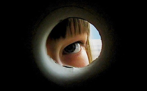 View of a child looking out a peephole, limiting what can be known
