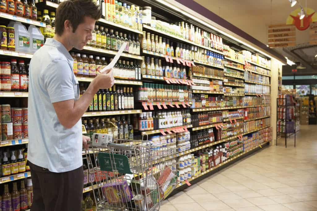Grocery shopping considering the list amid an aisle of teeming variety