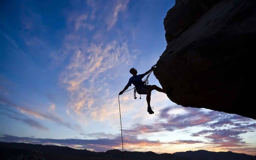 Mountain Climber Holding on by one hand over a vertical drop